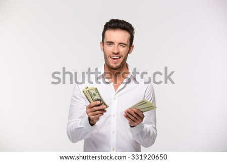 Portrait of a happy man holding dollar bills and winking isolated on a white background