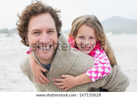 Portrait of a happy man piggybacking his cheerful daughter at the beach - stock photo