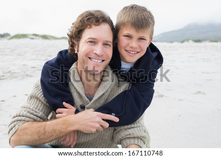 Portrait of a happy man piggybacking his cheerful son at the beach - stock photo