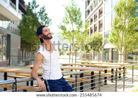 Portrait of a happy man relaxing with music on headphones - stock photo