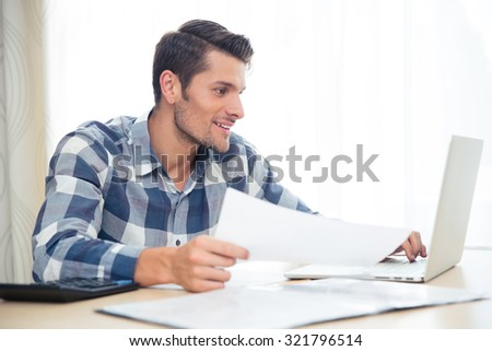 Portrait of a happy man sitting at the table with bills and laptop at home - stock photo