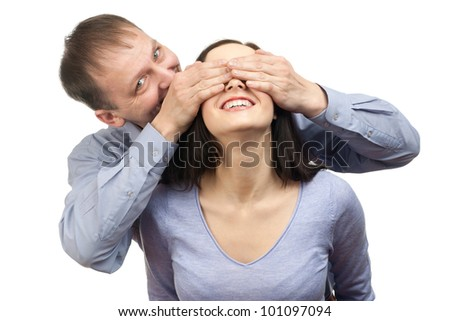 Portrait of a happy man surprising his wife by covering her eyes - stock photo