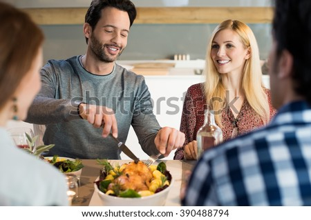 Portrait of a happy man taking his share of food. Happy family reunion at house. Young friend meeting for lunch at home. Friends having dinner or lunch at home. - stock photo