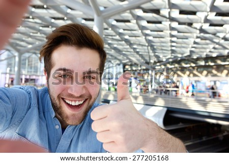Portrait of a happy man taking selfie with thumbs up - stock photo