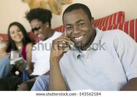 Portrait of a happy man using cellphone and blurred friends with camcorder in the background at home - stock photo