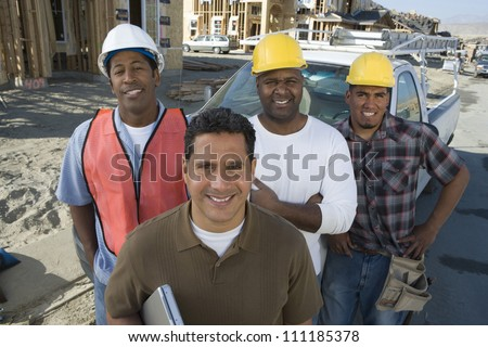 Portrait of a happy man with group of architects at construction site - stock photo