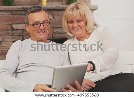 Portrait of a happy mature couple holding a digital tablet
