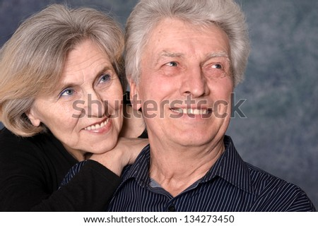 portrait of a happy mature couple over a gray background