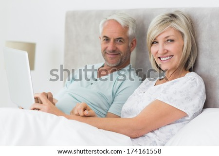 Portrait of a happy mature couple using digital tablet in bed at home