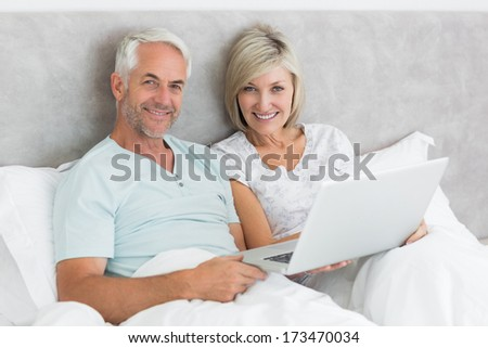 Portrait of a happy mature couple using laptop in bed at home