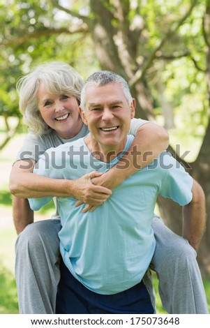 Portrait of a happy mature man carrying woman at the park - stock photo