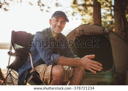Portrait of a happy mature man sitting in front of a tent and looking at camera. Senior caucasian man at campsite. - stock photo