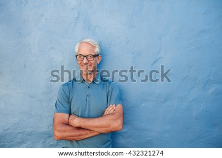 Portrait of a happy mature man standing with his arms crossed against a blue wall. Caucasian male wearing glasses looking away and smiling. - stock photo