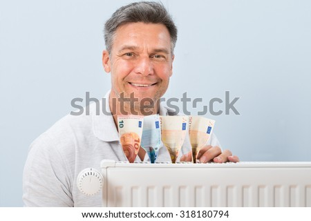 Portrait Of A Happy Mid-adult Man Placing Euro Notes On Radiator