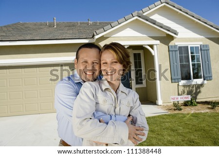 Portrait of a happy middle aged couple embracing in front of new house