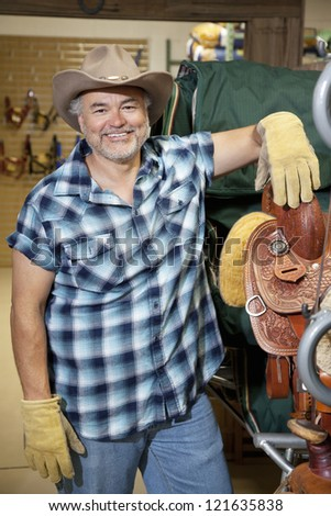 Portrait of a happy middle-aged cowboy standing by saddle in feed store - stock photo