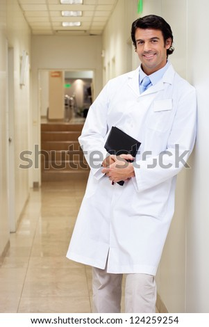 Portrait of a happy mixed race male doctor holding book while standing in hospital passageway - stock photo