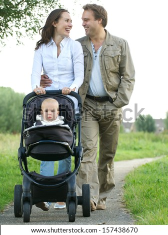 Portrait of a happy mother and father smiling and pushing baby pram with child