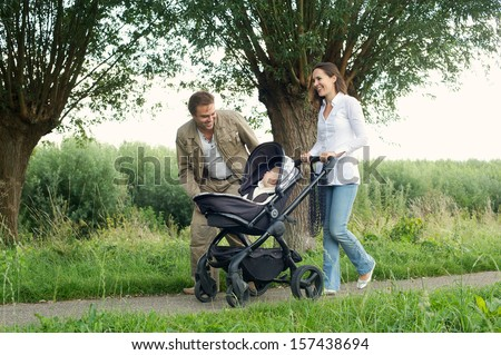 Portrait of a happy mother and father walking outdoors with baby in pram - stock photo