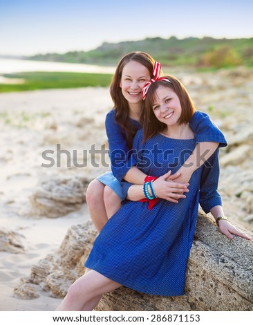 Portrait of a happy mother and her teen daughter on the beach