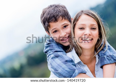 Portrait of a happy mother and son smiling outdoors - stock photo