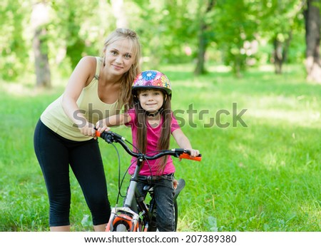 portrait of a happy mother embracing daughter who learns to ride a bike - stock photo