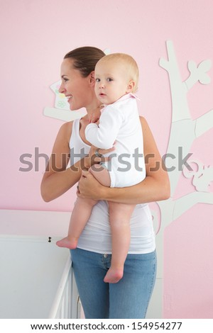 Portrait of a happy mother holding cute baby in bedroom