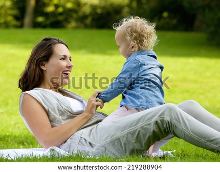Portrait of a happy mother playing with baby daughter outdoors - stock photo