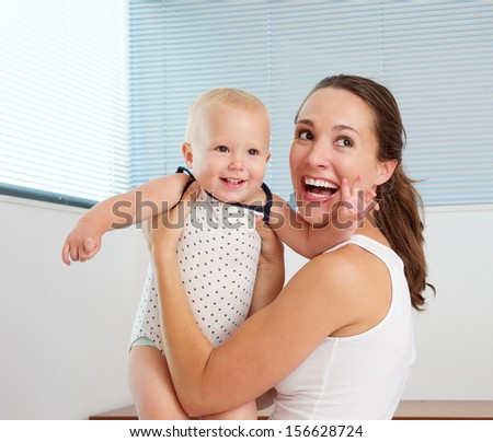Portrait of a happy mother playing with cute smiling baby at home