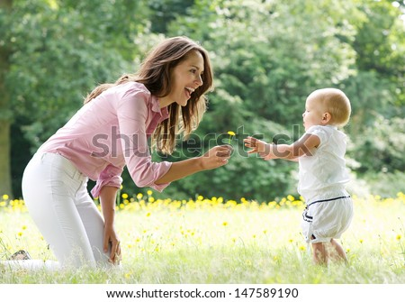 Portrait of a happy mother teaching baby to walk in the park - stock photo