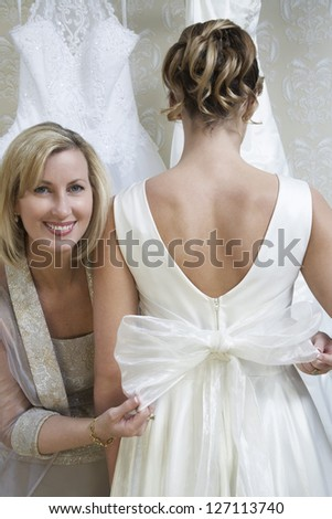 Portrait of a happy mother tying a white bow on a wedding dress of bride - stock photo
