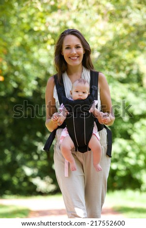 Portrait of a happy mother walking with infant in baby carrier   - stock photo
