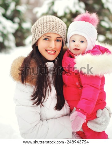 Portrait of a happy mother with child outdoors in the winter day