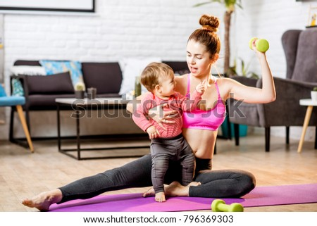 Portrait of a happy mother with her baby son exercising with dumbbells at home