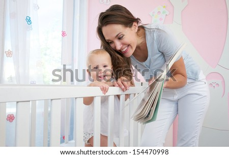 Portrait of a happy mother with smiling baby together in bedroom