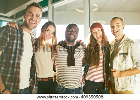Portrait of a happy multiethnic group of teens embracing and smiling - stock photo