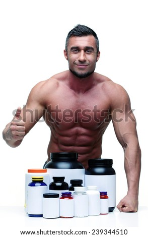 Portrait of a happy muscular man with thumbs up and sports nutrition