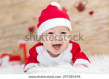 portrait of a happy newborn baby lying in Santa - stock photo