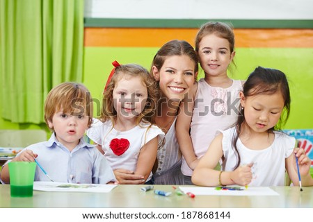 Portrait of a happy nursery woman and children together in a kindergarten - stock photo