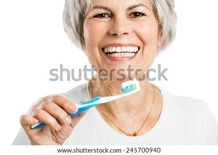 Portrait of a happy old woman brushing her teeth - stock photo