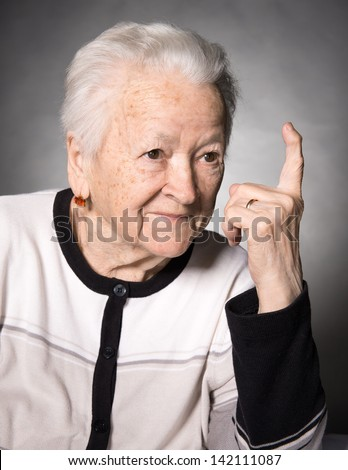 Portrait of a happy old woman pointing upwards on a gray background