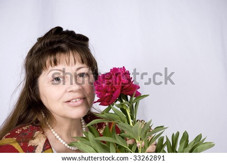 Portrait of a happy old woman with peony - stock photo