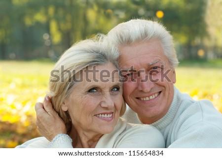 portrait of a happy older couple in autumn park - stock photo