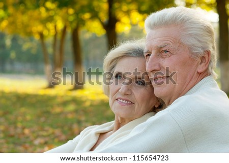 portrait of a happy older couple standing in autumn park