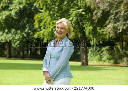 Portrait of a happy older woman smiling outdoors - stock photo