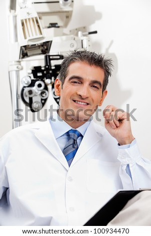 Portrait of a happy optometrist smiling while sitting in his office - stock photo