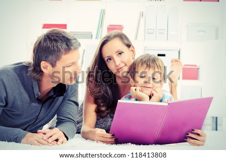 Portrait of a happy parents reading a book with their son. - stock photo