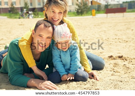 portrait of a happy playing family outdoors. young parents with daughter in the summer. Mom, dad and child