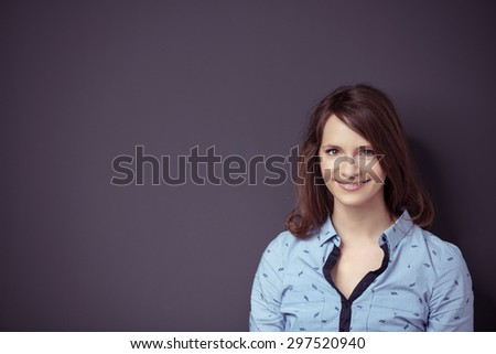 Portrait of a Happy Pretty Girl Against Gray Wall Background with Copy Space, Smiling at the Camera. - stock photo