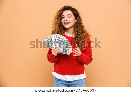 Portrait of a happy pretty girl holding bunch of money banknotes and celebrating isolated over beige background